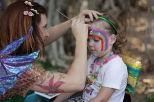 lara face painting a rainbow on a girl in the park